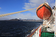 Hurtigruten coastal cruise ship leaves town of Harstad in its wake as it sails in early May along north coast of Norway.