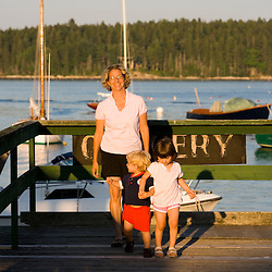 A mom and her young kids walk in the pier at Holbrooks Wharf  in Cundy's Harbor, Maine.