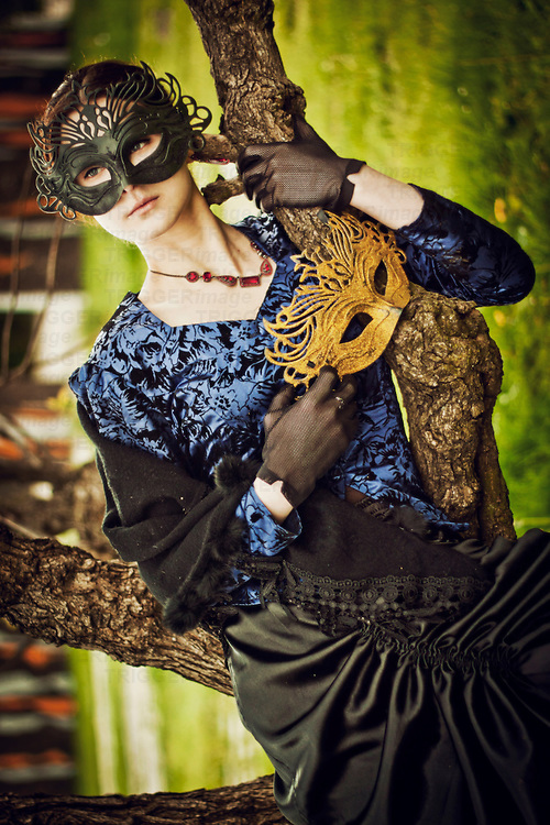 atmospheric photo of beautiful young caucasian woman in gothic gown with black mask on her  face, standing among the trees holding golden mask in one hand