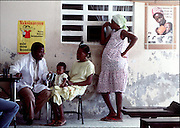 A doctor in rural Haiti counsels woman on the need to vacinate.