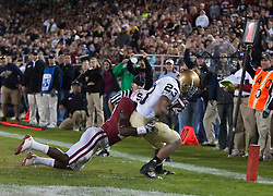 November 28, 2009; Stanford, CA, USA;  Notre Dame Fighting Irish wide receiver Golden Tate (23) makes a touchdown catch in front of Stanford Cardinal cornerback Johnson Bademosi (27) during the first quarter at Stanford Stadium.   Stanford defeated Notre Dame 45-38.