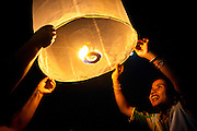 Revelers of the traditional Thai festival held on the full moon of the second month of the ancient Lanna Calender, Yi Peng, release paper laterns, into the sky in Chiang Mai, Thailand on Monday, Nov. 22, 2010. The ancient capital of the former Lanna kingdom, where now both Loi Krathong and Yi Peng are celebrated at the same time, result in paper lanterns being lit and floral boats floating on the waters.<br />