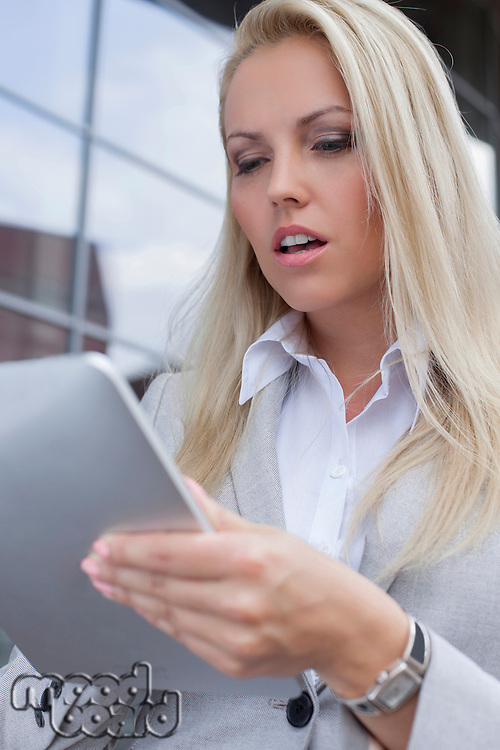 Beautiful businesswoman using digital tablet outdoors
