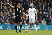 Referee Andre Marriner shows Liverpool midfielder Jordan Henderson (14)   the way during the Barclays Premier League match between Crystal Palace and Liverpool at Selhurst Park, London, England on 6 March 2016. Photo by Simon Davies.