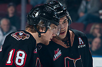 KELOWNA, BC - FEBRUARY 17: Riley Stotts #18 and Jett Woo #22 of the Calgary Hitmen stand on the ice and strategize against the Kelowna Rockets at Prospera Place on February 17, 2020 in Kelowna, Canada. (Photo by Marissa Baecker/Shoot the Breeze)