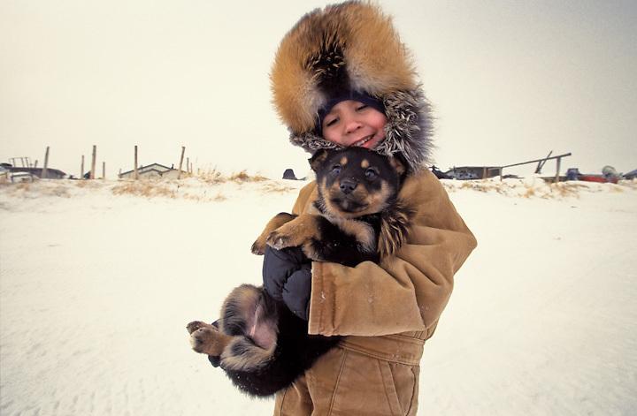 "Iditarod observer, Stuart Isaah Towarak in a fox hat with his dog, ""Lucky"",  in the Iñupiaq village of Unalakleet, Alaska."