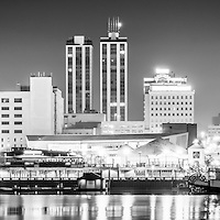 Peoria Illinois skyline panorama black and white picture at night. Includes downtown Peoria city skyline buildings along the Illinois River. Panorama photo ratio is 1:3.