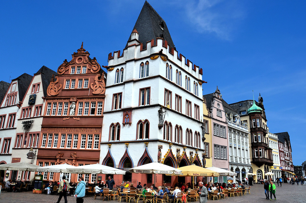 Steipe and Red House in Trier, Germany <br /> The white building along Dietrichstrasse and the Main Market of Tier is called the Steipe.  It was built in the mid-15th century for entertaining the towns&rsquo; visiting dignitaries.  Perched above the outdoor restaurant are reproduced sculptures of three Apostles and St. Helena.  The neighbor on the left is the Red House, a 17th century baker&rsquo;s guild. It&rsquo;s here that an inscription claims that Trier is 1300 years older than Rome.