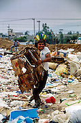 CIUDAD NEZAHUALCOYOTL, DF, MEXICO: A man carries a stack of cardboard through the garbage in the Ciudad Nezahualcoyotl dump on the edge of Mexico City. Hundreds of people live in the dump and make a living by scavenging through the refuse brought to the dump by Mexico City's garbage trucks.  PHOTO ©  JACK KURTZ   POVERTY  HOMELESS  ECONOMY   SOCIAL ISSUES   LABOUR