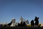 Silhouetted people and the City of London skyline (the capital's financial district - aka the Square Mile seen from across the river Thames on the Southbank, on 26th September 2018, in London, England.