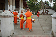"""Mar. 15, 2009 -- LUANG PRABANG, LAOS:  Buddhist Monks in Luang Prabang, Laos, gather before going about their """"Tak Bat,"""" Lao for """"monks morning rounds."""" The monks collect alms in the form of food from people who line their route. For the monks, it is the only food they get that day, for the people it's a chance to """"make merit."""" Luang Prabang is a UNESCO World Heritage Site and the spiritual capital of Laos. There are dozens of """"wats"""" or temples and thousands of monks in the city. It is still the center of Buddhist education in Laos. Photo by Jack Kurtz"""