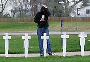 Wendy Becker of Littleton pauses at crosses near the site of the Columbine High School tragedy on the sixth anniversary of the event in Littleton, Colorado April 20, 2005. Each cross was a rememberance for the 12 students and one teacher killed in the attack.  REUTERS/Rick Wilking