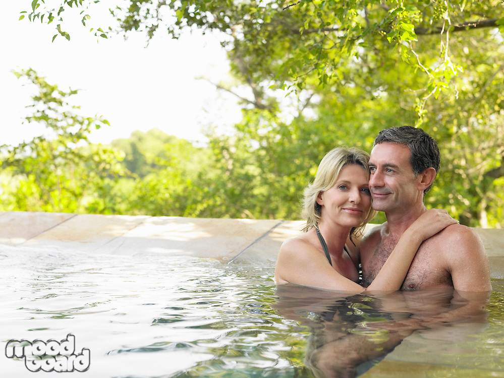 Portrait of adult couple embracing in pool smiling