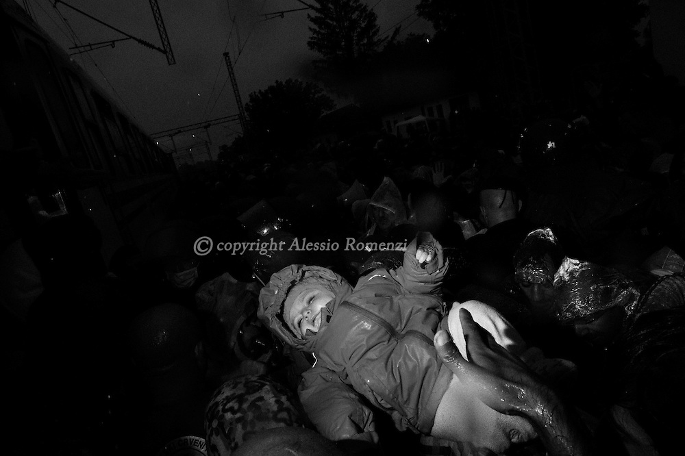 Croatia: A migrants child is lifted as hundreds of desperately try to board a train heading for Zagreb from Tovarnik station. Alessio Romenzi