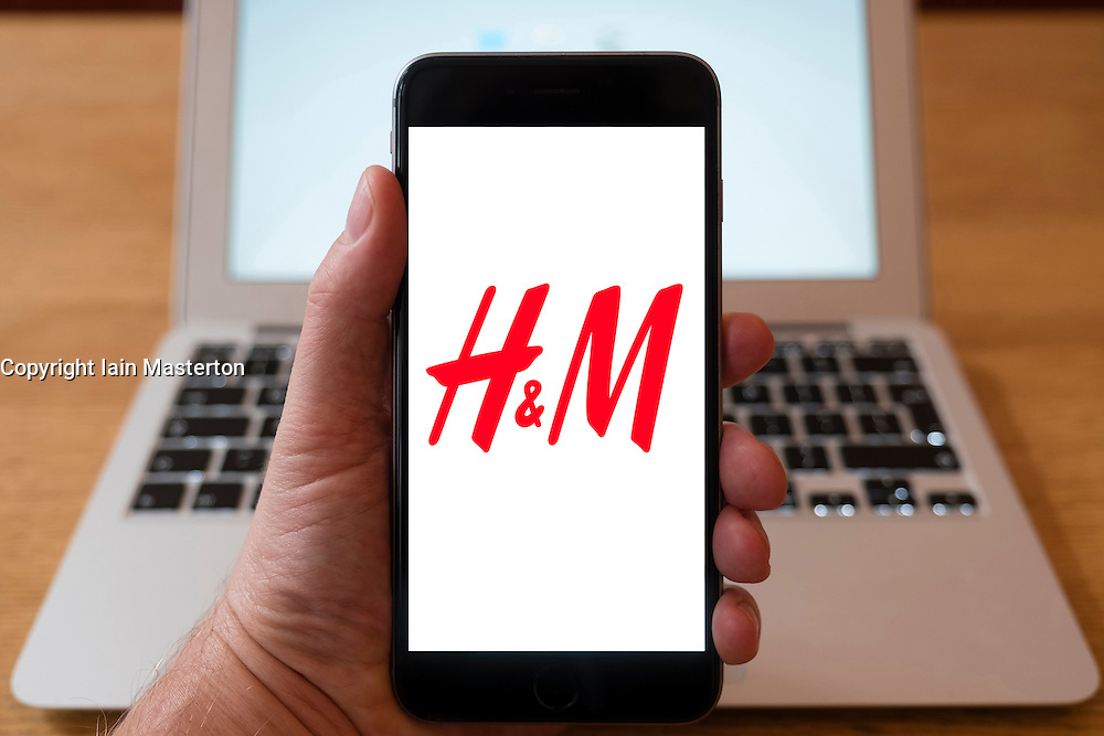 Using iPhone smartphone to display logo of H&M high street fashion retailer