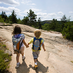 Two young hikers (girl age 5 and boy age 3) on the South Bubble in Maine's Acadia National Park.  Near Jordan Pond.