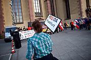 Frankfurt am Main | 21 Apr 2015<br /> <br /> Am Dienstag (21.04.2015) hielt die rassistische und islamfeindliche Gruppe PEGIDA (Patriotische Europ&auml;er gegen die Islamisierung des Abendlandes) an der Hauotwache neben der Katharinenkirche in Frankfurt am Main eine Mahnwache unter dem Motto &quot;Wir sind wieder da&quot; ab. Die Kundgebung war wie immer mit Hamburger Gittern abgesperrt und von starken Polizeikr&auml;ften bewacht. Etwa 1000 Menschen nahmen an den Gegenprotesten teil.<br /> Hier: Teilnehmerin der PEGIDA-Kundgebung mit einem kleinen Plakat mit der Aufschrift &quot;PEGIDA Frankfurt&quot;.<br /> <br /> &copy;peter-juelich.com<br /> <br /> [Foto Honorarpflichtig | No Model Release | No Property Release]