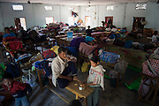 Bato and his wife Mary Rengma of the Khanari Village enjoy the relative quiet during the day in a classroom turned bedroom of approximately 200. Families have resorted to used school benches draped with sheets as walls between family areas. Image © Jonah Markowitz/Falcon Photo Agency