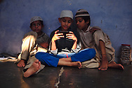Students at a madrasa inside a small mosque of Old Delhi.