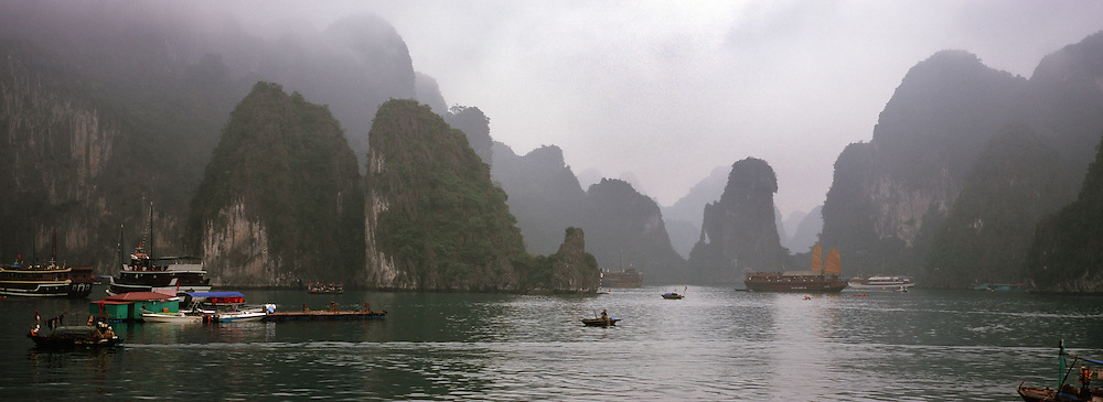 A local fisherman tends to the fishing nets in the early morning mist in Ha Long Bay, Vietnam. The bay consists of a dense cluster of 1,969 limestone monolithic islands. Ha Long Bay, is a UNESCO World Heritage Site, and a popular tourist destination. Ha Long, Bay, Vietnam.  Photo Tim Clayton