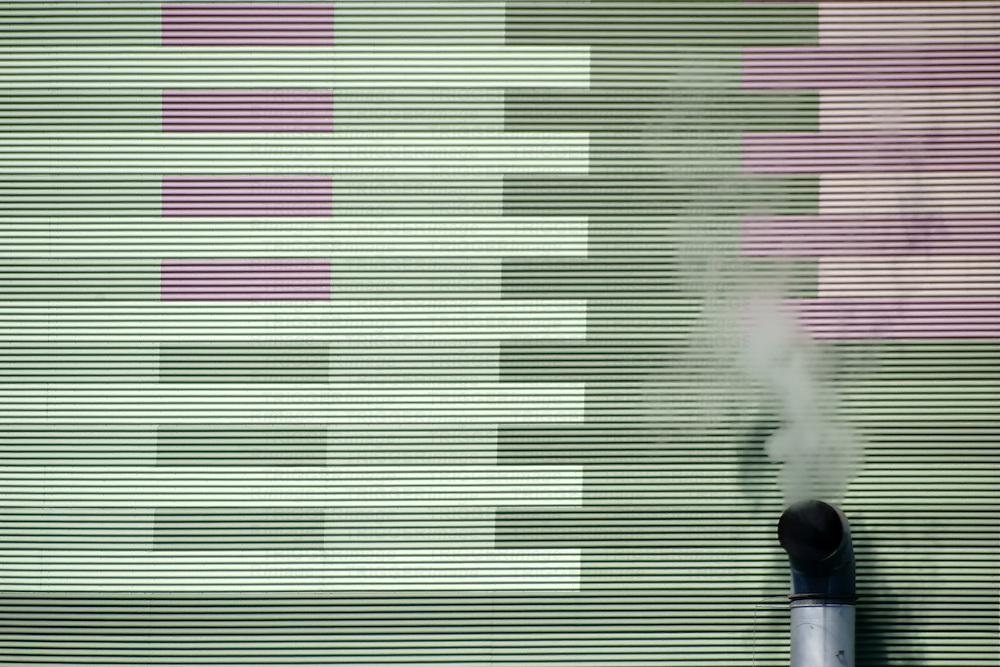 The smoky chimney of an industrial plant on the outside wall of a power plant.