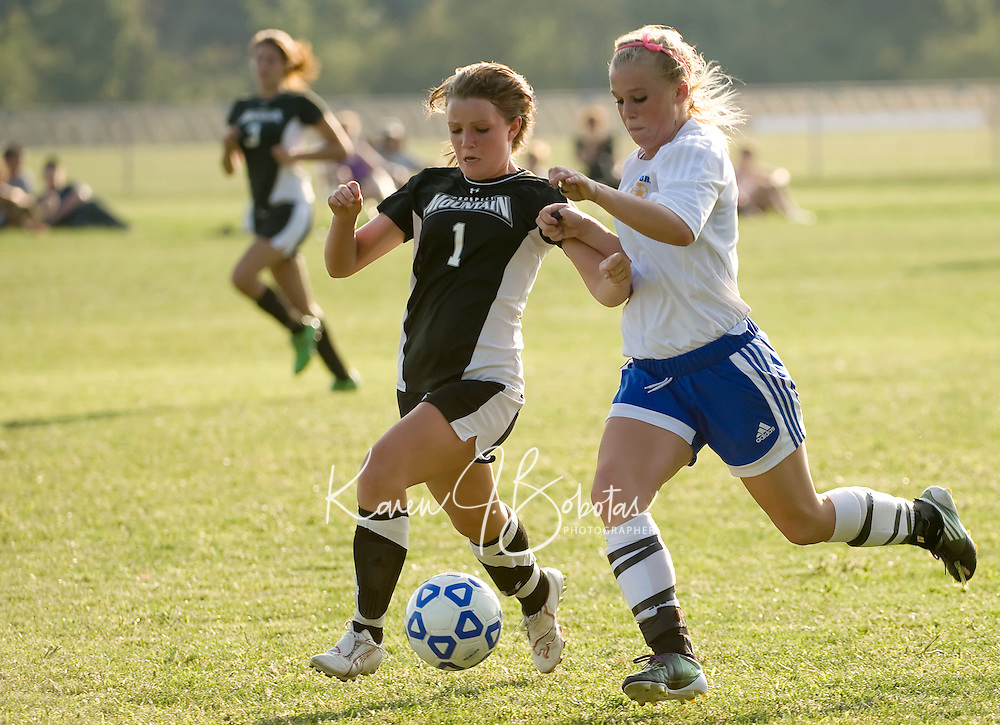 Prospect Mountain's Nicole Dwyer and Gilford's Chelsea Crockett battle for possession of the ball during Tuesday afternoon's NHIAA division III game.   (Karen Bobotas/for the Laconia Daily Sun)