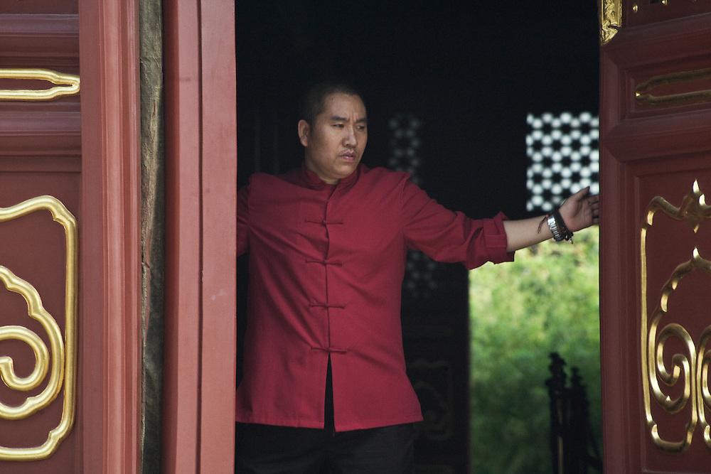 L'un des gardiens du Temple des lamas referme les grandes portes du hall d'assemblée pour le soir.