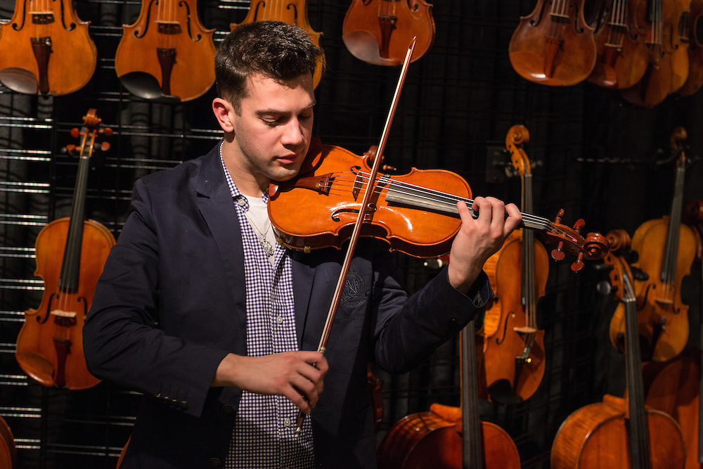 Johnny Weizenecker, a music student at Gettysburg College, tries a violin made by contemporary Genovese luthier Pio Montanari in the booth of Boston's Pal Dulude.