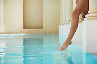 Young woman stepping into swimming pool low section