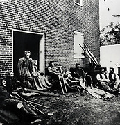 American Civil War: Wounded soldiers in care of the Red Cross sitting out in the fresh air. Photograph.