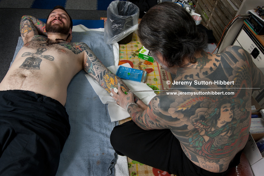 Horiyoshi III (the 3rd) (right of pic), expert Japanese tattooist, adds colour to a tattoo on the forearm of his German understudy Alex Reinke (also known as Horikitsune) (left of pic), in Horiyoshi's studio in Yokohama, Japan, on Saturday 10th September 2011. The golden dragon Koi carp jumping upwards portrays good luck.