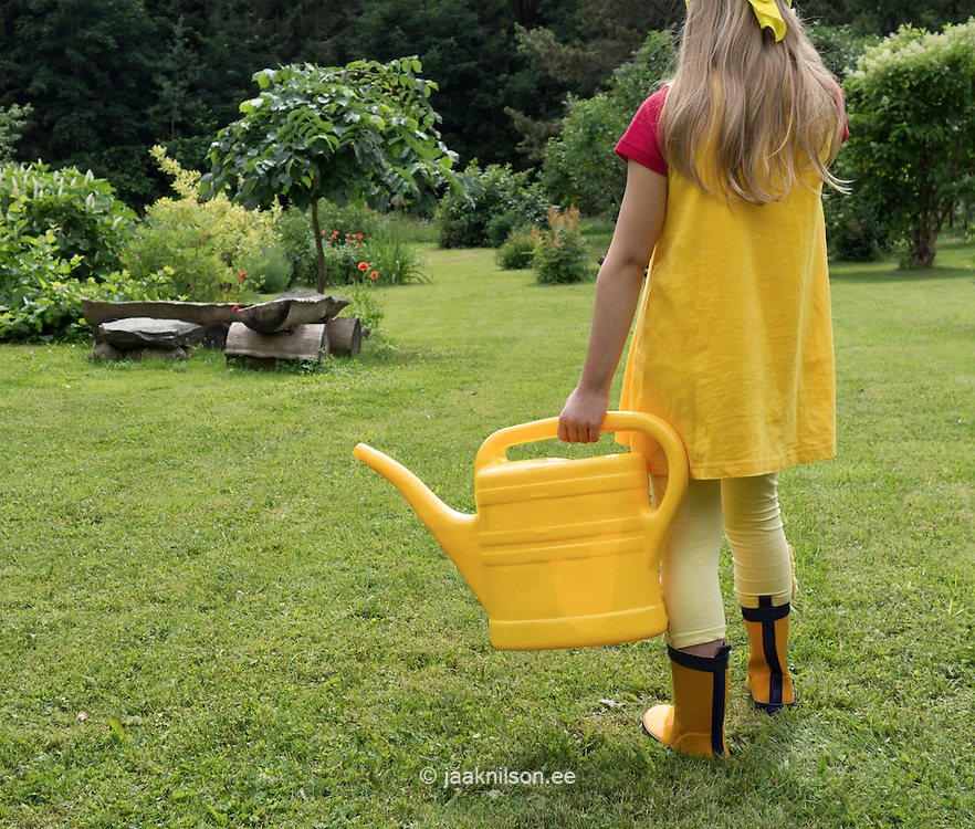 Child, girl standing and holding watering can in garden. Yellow clothing and wellies. Gardening.