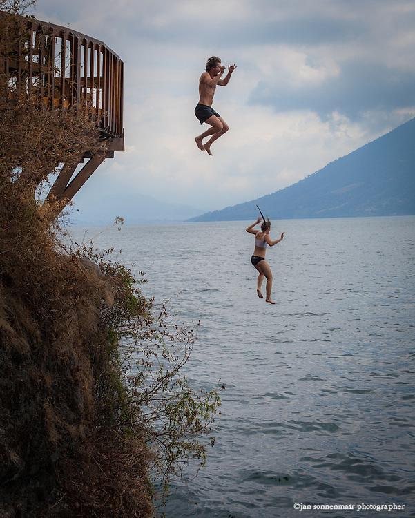 Lake Atitlan, Guatemala.  Two swimmers dive off Las Rocas near the village of San Marcos La Laguna
