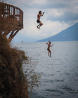 Lake Atitlan, Guatemala.  Two swimmers dive off Las Rocas near the village of San Marcos La Laguna