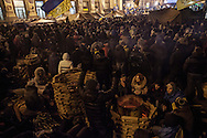 Anti government protesters warm themselves as they stand guard on one of the barricades surrounding Maidan square that is occupied by the protesters. Thousands of people have been protesting against the government since a decision by Ukrainian president Viktor Yanukovych to suspend a trade and partnership agreement with the European Union in favor of incentives from Russia. 14 December 2013.