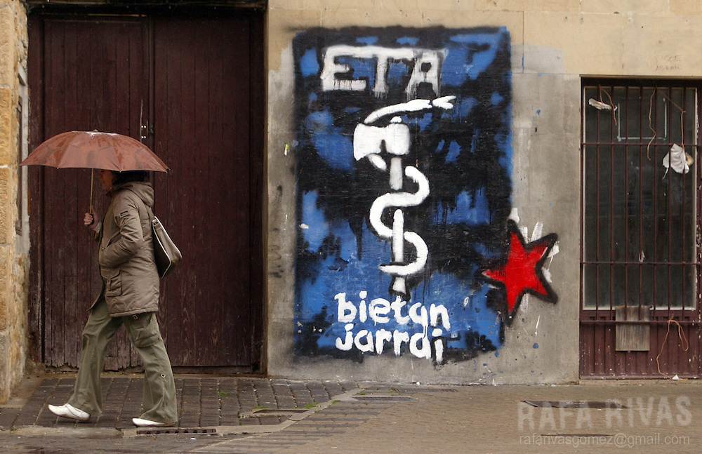 A woman walks past a graffiti representing the pro-independence armed Basque group ETA logo, 23 March 2006 in the northern Spanish village of Alsasua, Navarra province. PHOTO RAFA RIVAS