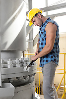 Side view of young manual worker using wrench on industrial machine
