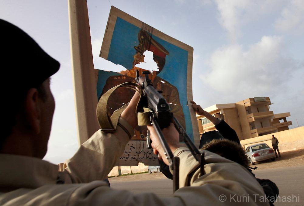 Rebel militia agasint Col. Muammar Gaddafi shoots a poster of Gaddafi in As Sider on March 5, 2011..Photo by Kuni Takahashi
