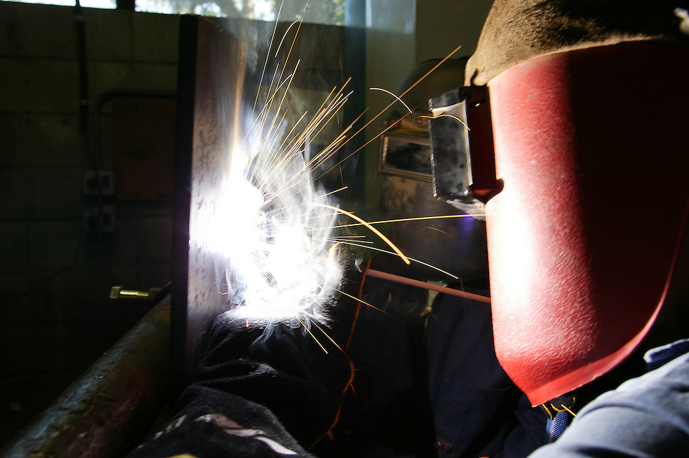 Welding sparks fly as a welder works on a project at an engineering works, New Plymouth, New Zealand, March 31, 2004. Credit:SNPA / Rob Tucker