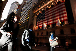 People walk past the New York Stock Exchange in Wall Street sign in New York, New York, USA, 23 October 2008. As Wall Street descend into a financial turmoil not seen since the stock market crash of 1929 and financial businesses were pommeled into rampant sell-offs in stocks and face regulatory changes to their business practices, professionals and non-professionals working in the district's banks, stock-trading houses and insurance companies are showing stress and a gloom not unlike the times of the Great Depression.