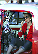 A Rockabilly girl sitting in a red customised Hotrod car sucking on a lollypop, Viva Las Vegas Festival, Las Vegas, USA 2006.