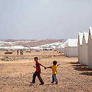 Children walk through Azraq refugee camp in Jordan, two weeks after it opened in May 2014. The desert camp was built to accommodate the growing influx of refugees escaping the war in neighboring Syria. As of May 2018, 662,000 of the 5.6 million registered Syrian refugees live in Jordan.