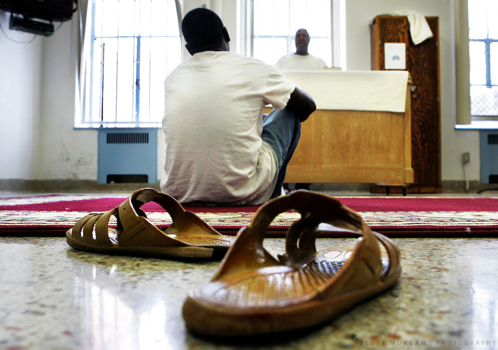 Scott Morgan/The Hawk Eye.Yousif Suliman's sandals sit behind him as he listens to Imam Ronnie Matlock read from the Quran Friday April 14, 2006 during a service at the Mount Pleasant Correctional Facility.