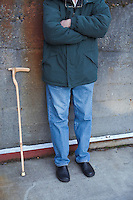 Man standing against concrete wall with walking cane leaning on wall by his side .