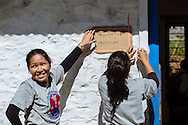 Anita Gurung (left), a volunteer with Himalayan Family Healthcare Project, hangs signs with another Nepali volunteer outside makeshift clinics at a school in Thonche, Nepal.