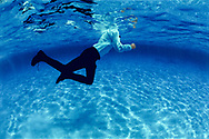 Dropped into the deep end, man in fukl clothes trying to swim in deep water.