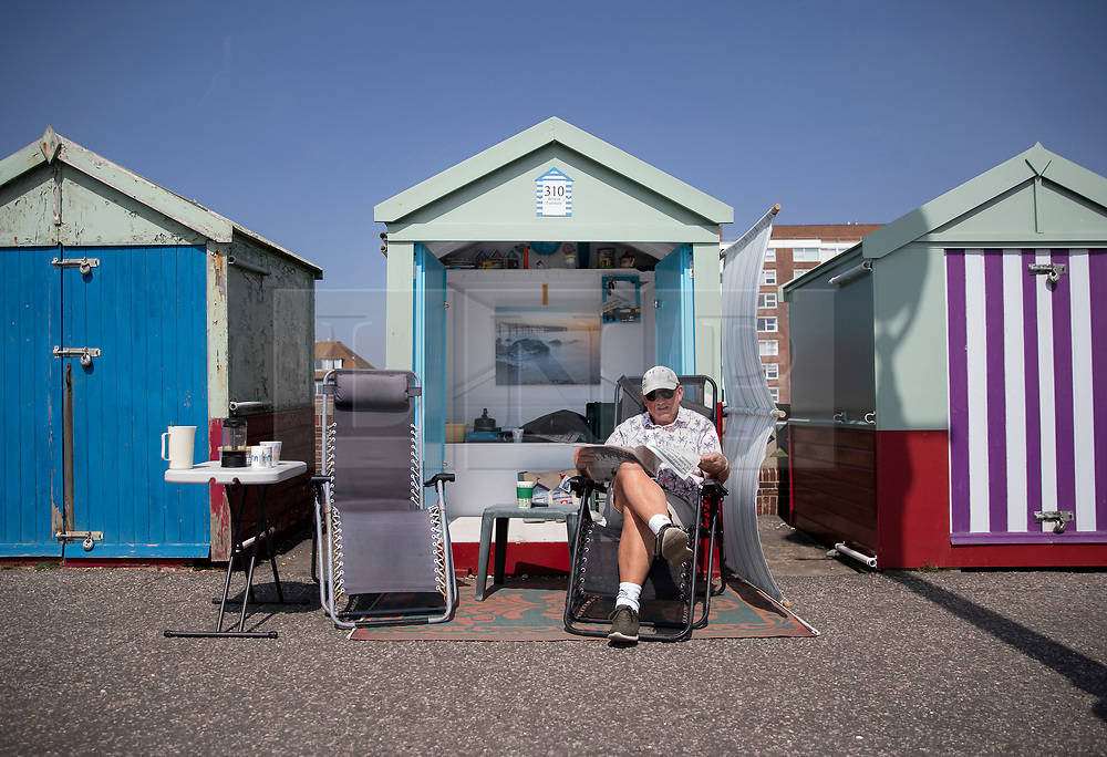 © Licensed to London News Pictures. 22/04/2019. Brighton and Hove, UK. A man reads his newspaper outside a beach hut on the Western Esplanade at Hove, West Sussex as most of the UK enjoys record breaking high Easter weekend temperatures. Photo credit: Peter Macdiarmid/LNP