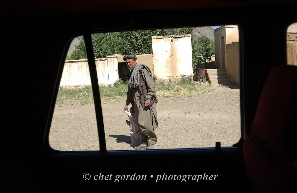 "An Afghan man seen through the window of a car at the Charasyab health clinic approximately 20 kilometers outside of Kabul, Afghanistan on Sunday, May 26, 2002. A humanitarian mission organized by The Geshundheit Instititute, founded by Dr. Hunter ""Patch"" Adams, Lufthansa Cargo, and DHL Worldwide Express collaborated to ship medicines, food and orthopedic supplies to the Indira Ghandi Children's Hospital, clinics and orphanages in Kabul. The German NGO (Non Governmental Organization) Hammer Forum supervised the distribution of the donated supplies from various non-profit organizations in the U.S. and The Netherlands."