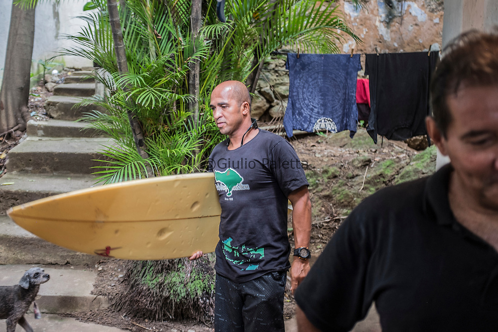 "Claudio ""Pamonha"" at Carlos Augusto's house (right), 55, surfer. He represents Rocinha's first generation of surfers in the 70s. Also grew up in Rua 2, says that he has been through a dark past but now was saved by evangelical church. He's one of the men who still inspiring new slum surfers, and told me about the ways the beachbreak changed over the course of the years, from the beginning of shoreline deck until the construction of the channel that dumps Rocinha sewage directly at Cantão"