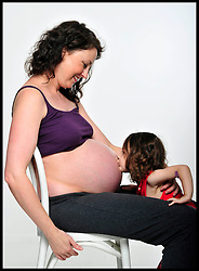 A Pregnant Mother at 37 weeks, with her 2 year old daughter,  holds on to her bump as she is expecting a boy, Saturday July 7, 2012. Photo by Andrew Parsons/i-Images..All Rights Reserved ©Andrew Parsons/i-Images.See Instructions